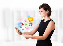 Young woman looking at modern tablet with colourful icons Stock Images