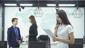 Business people working in office. Young business woman looking at the report against the background of two employees - man in formal costume and woman talking stock video