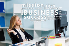 Young business woman looking on word's cloud. Young pretty business woman looking on word's cloud in the blue office stock image
