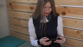 Young business woman looks at the mobile phone, on her hand a new smart watch stock footage