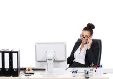 Young business woman looks over her glasses. Young, beautiful business woman sits at the desk in the office and looks over her glasses Stock Images