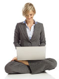 Young Business woman in a lotus pose with laptop. Young Business woman smiling in a lotus pose with laptop Royalty Free Stock Image