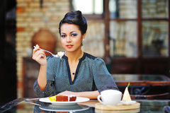 Young business woman on lunch break in cafe or restaurant holdin Stock Photos