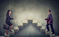 Young business woman and man stepping up a stairway career ladder stock photos