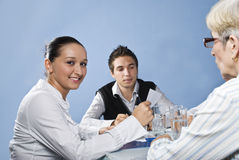 Young business woman in middle of meeting. Young business woman smiling and holding a paper in her hands in middle of a meeting with her colleagues,check also Royalty Free Stock Image
