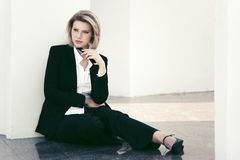 Young business woman with a mobile phone sitting at the wall Royalty Free Stock Photo