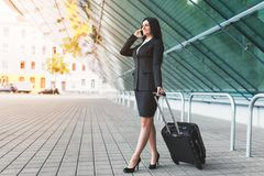 Young business woman with mobile phone and suitcase in urban setting. Young beautiful business woman with mobile phone and suitcase in urban setting Royalty Free Stock Photos
