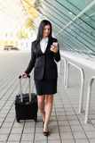 Young business woman with mobile phone and suitcase in urban setting. Young beautiful business woman with mobile phone and suitcase in urban setting Royalty Free Stock Photo