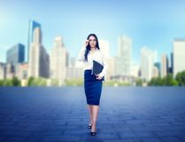 Young business woman with notebook in hand. Portrait of young business woman in glasses and white blouse with notebook in hand, skyscaper on background. Modern Royalty Free Stock Images