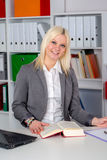 Young business woman in office. Young blond business woman in the office looking friendly in to the camera Royalty Free Stock Photos