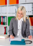 Young business woman in office. Young blond business woman in the office is writing Stock Photography