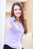 Young business woman in office giving thumb-up Royalty Free Stock Photos