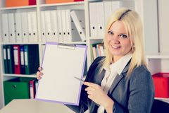 Young business woman in office pointing at clipboard. Young blond business woman in the office pointing at clipboard Royalty Free Stock Images