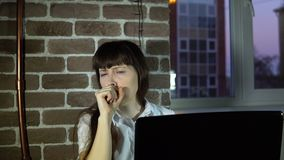 Young business woman at office with a sore throat. A young business woman coughs, covering her mouth with her hand, frowns then sells to work on the laptop in stock video footage