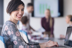 Young business woman at office working on laptop with team on me Royalty Free Stock Images