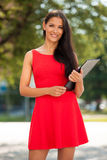 Young business woman outdoors on a summer day. Young business woman with a work folder and a pen outdoors on a summer day Royalty Free Stock Photo