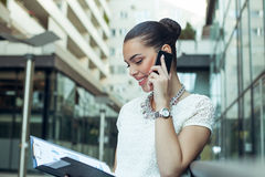 Young business woman outside on phone Stock Photo