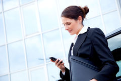 Young business woman outside, reading sms Royalty Free Stock Image