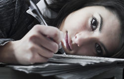 Young business woman overwhelmed by her job. Young and stressed business woman looking sad and overwhelmed by paperwork with her head laying on the table. Focus Stock Photos