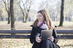 Young business woman in the park buys online Royalty Free Stock Image