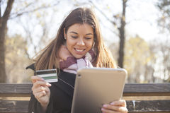 Young business woman in the park buys online Royalty Free Stock Photography