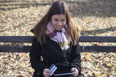 Young business woman in the park buys online Stock Image
