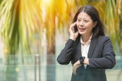 Young business woman on phone call. Looking away outdoor office, checking smartwatch while talking on mobile phone. beautiful mixed race asian chinese Royalty Free Stock Images