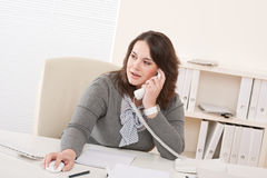 Young business woman on phone at office Royalty Free Stock Image