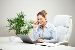 Young business woman on the phone at the office. Young business woman talking on the phone at the office Stock Photography