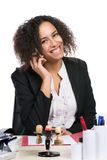 Young business woman phones. Young, beautiful business woman sits at the desk in the office and phones with a smart phone Royalty Free Stock Image