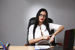 Young business woman pointing a finger at the clock it was time Royalty Free Stock Photography