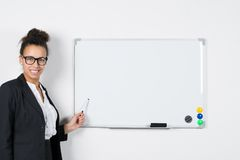 Young business woman points at board. Young business woman points with a pen at a white magnetic board Stock Photography