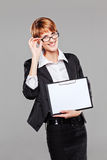 Young business woman presenting a clipboard and holding her glasses Royalty Free Stock Image
