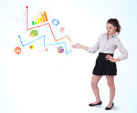 Young business woman presenting colorful charts and diagrams Royalty Free Stock Images