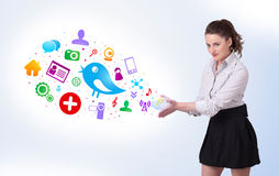 Young business woman presenting colourful social icons Stock Image