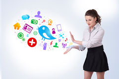Young business woman presenting colourful social icons Stock Images