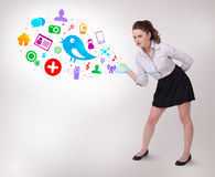 Young business woman presenting colourful social icons Royalty Free Stock Image
