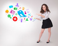 Young business woman presenting colourful social icons. On bright background Royalty Free Stock Photos