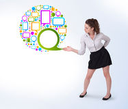 Young business woman presenting colourful speach bubble. On bright background Royalty Free Stock Photography