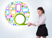 Young business woman presenting colourful speach bubble. On bright background Royalty Free Stock Images