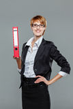 Young business woman presenting folder with her right hand and smiling Stock Photos