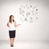 Young business woman presenting hand drawn media icons Royalty Free Stock Photo