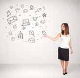 Young business woman presenting hand drawn media icons Stock Photos