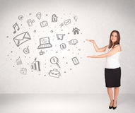 Young business woman presenting hand drawn media icons Royalty Free Stock Photos