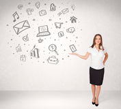 Young business woman presenting hand drawn media icons Stock Photo