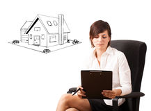 Young business woman presenting a house on whiteboard Royalty Free Stock Photos