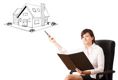 Young business woman presenting a house on whiteboard Stock Image