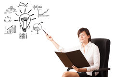 Young business woman presenting light bulb with various diagrams Royalty Free Stock Photo