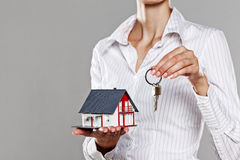 Young business woman presenting a model house and keys Royalty Free Stock Images