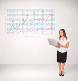 Young business woman presenting stock market diagram Stock Photo